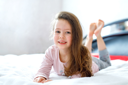 Adorable happy little kid girl after sleeping in his white bed in colorful nightwear. Foto de archivo