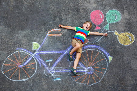 Happy little kid boy having fun with bicycle and air balloons picture drawing with colorful chalks on asphalt.