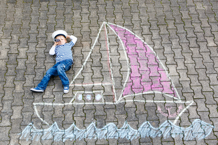 Little kid boy as pirate on ship or sailing boat picture painting with colorful chalks on asphalt.