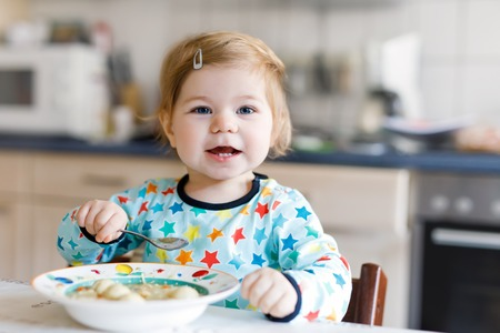 Adorable baby girl eating from spoon vegetable noodle soup. food, child, feeding and development concept. Cute toddler, daughter with spoon sitting in highchair and learning to eat by itself
