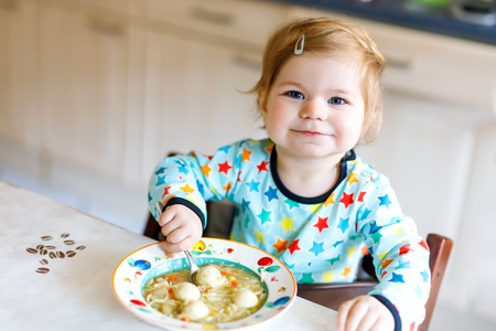 Adorable baby girl eating from spoon vegetable noodle soup. food, child, feeding and people concept Stock Photo