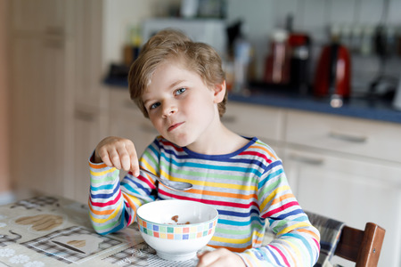Happy little blond kid boy eating cereals for breakfast or lunch. Healthy eating for children. 스톡 콘텐츠