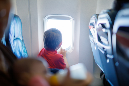 Little kid boy looking outside of plane window during flight on airplane. Stock Photo