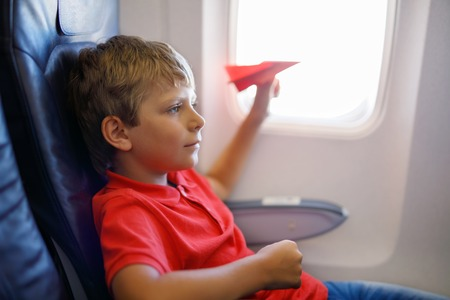Little kid boy playing with red paper plane during flight on airplane Stock Photo