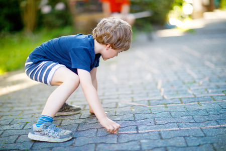 Little blond funny kid boy playing hopscotch on playground outdoors