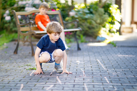 Two little school and preschool kids boys playing hopscotch on playground