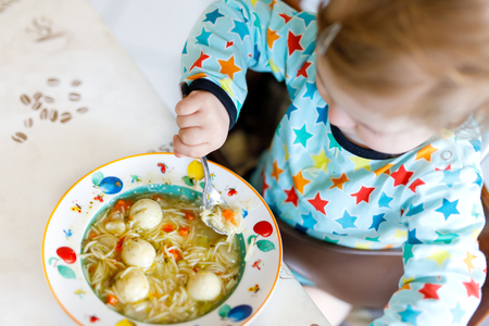 Adorable baby girl eating from spoon vegetable noodle soup. food, child, feeding and people concept Stock fotó