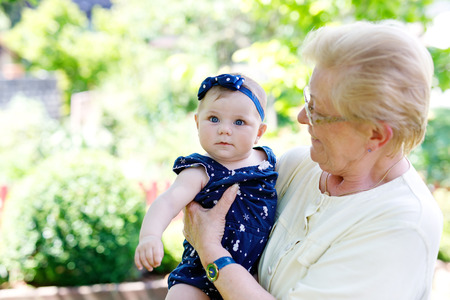 Cute little baby girl with grandmother on summer day in garden Stock Photo