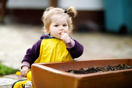 Cute adorable toddler girl playing with sand and shovel on spring day. Baby child wearing yellow boots and mud rain puddle pants. Фото со стока