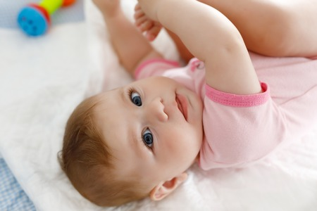 Cute baby taking feet in mouth. Adorable little baby girl sucking foot.