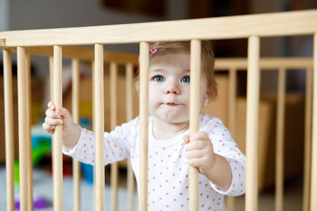 Beautiful little baby girl standing inside playpen. Cute adorable child playing with colorful toy