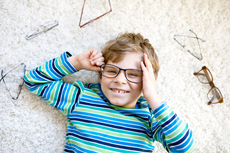 Close-up portrait of little blond kid boy with brown eyeglasses 写真素材