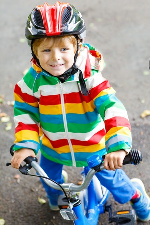 Little cute kid boy on bicycle on summer or autmn day. Healthy happy child having fun with cycling on bike.
