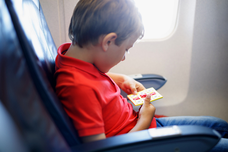 Little kid boy playing tic tac toe game during flight on airplane. Imagens - 99689843