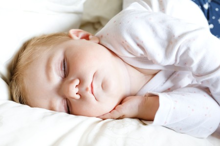 Cute adorable baby girl of 6 months sleeping peaceful in bed