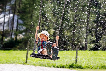 Funny kid boy having fun with chain swing on outdoor playground while being wet splashed with water Imagens