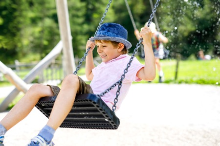 Funny kid boy having fun with chain swing on outdoor playground while being wet splashed with water Banco de Imagens