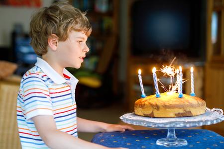 Adorable happy blond little kid boy celebrating his birthday.