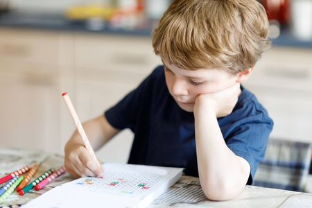 Tired kid boy at home making homework writing letters with colorful pens Stock Photo