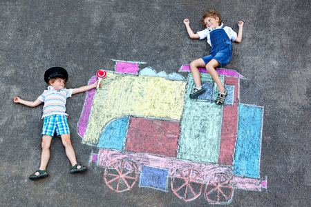 Two little kids boys having fun with train chalks picture