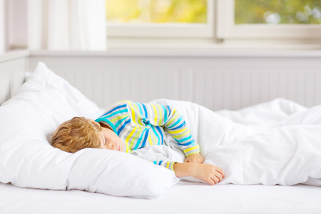 happy little kid boy after sleeping in bed in colorful nightwear Stock Photo