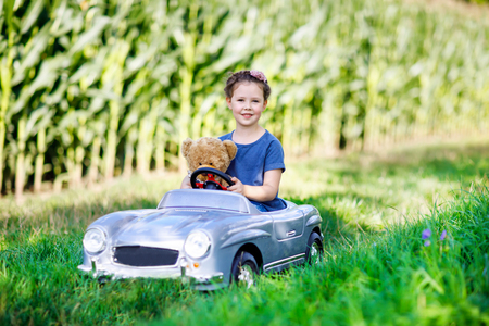 Little preschool kid girl driving big toy car and having fun with playing with big plush toy bea