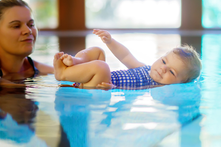 Happy mother swimming with cute adorable baby girl daughter in swimming pool spending spa vacations