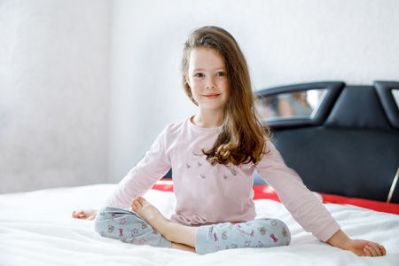 Adorable happy little kid girl after sleeping in his white bed in colorful nightwear. School child making baby yoga exercises