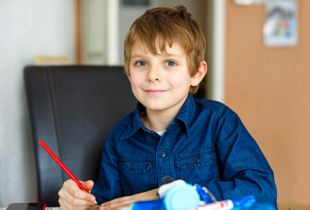 Cute little kid boy with glasses at home making homework, writing letters with colorful pens.