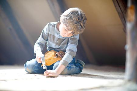 Kleiner Junge, der mit Spielzeugwerkzeugen auf Baustelle hilft. Standard-Bild