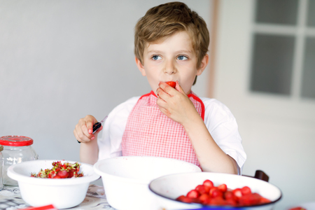 Little blond kid boy helping and making strawberry jam in summer