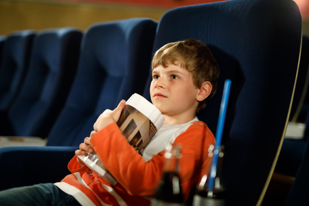 cute blond little kid boy eating popcorn at the cinema before the movie starts. Happy child having fun and waiting for the cartoon or film