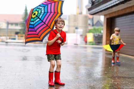 Kid boy wearing red rain boots and walking with umbrella