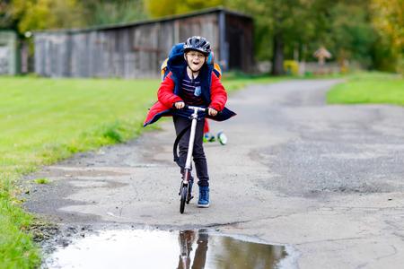 Cute preschool kid boy riding on scooter to school