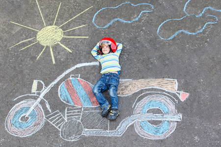 Little child in helmet with motorcycle picture drawing with colo