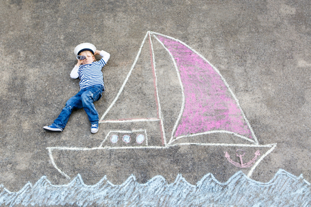 Little kid boy as pirate on ship or sailingboat picture painting with colorful chalks on asphalt. Imagens