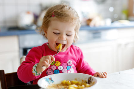Adorable baby girl eating from fork vegetables and pasta. food, child, feeding and development concept