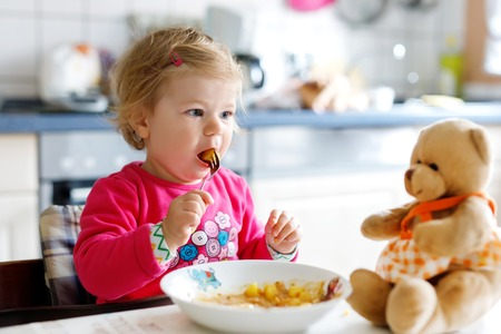 Adorable baby girl eating from fork vegetables and pasta. Little child feeding and playing with toy teddy bear.