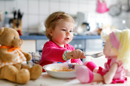 Adorable baby girl eating from fork vegetables and pasta. Little child feeding and playing with toy doll Stock Photo - 102801478