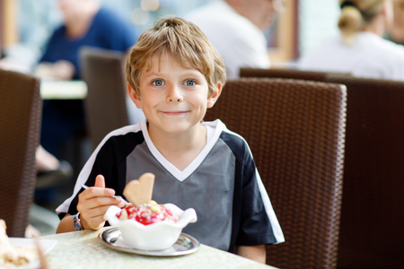 Little kid boy eating ice cream in outdoor cafe or restaurant. 写真素材