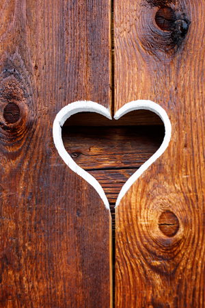 Wooden fence with heart. Part of a window in Tirol, Austria Imagens