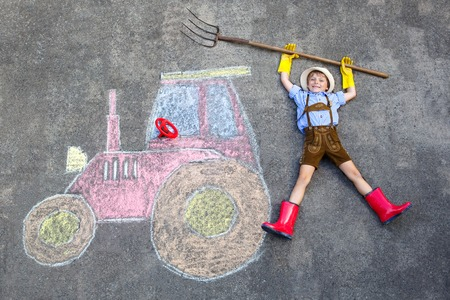 little kid boy having fun with tractor chalks picture Stock Photo