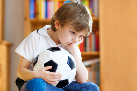 Sad and not happy little kid with football about lost football or soccer game. child after watching match on tv 免版税图像