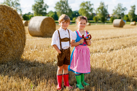 Two kids, boy and girl in traditional Bavarian costumes in wheat field Standard-Bild - 101729355