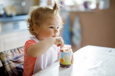 Adorable baby girl eating from spoon vegetables or fruit canned food, child, feeding and development concept.
