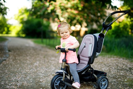 Cute adorable toddler girl sitting on pushing bicyle or tricycle. Little baby child going for a walk with parents on sunny day. Standard-Bild