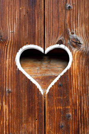 Wooden fence with heart. Part of a window in Tirol, Austria Stock fotó