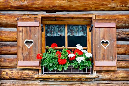 Fenêtre en bois typiquement bavarois ou autrichien avec des fleurs de géranium rouge sur maison en Autriche ou en Allemagne