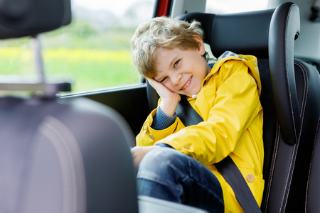 Adorable cute preschool kid boy sitting in car in yellow rain coat. Stok Fotoğraf