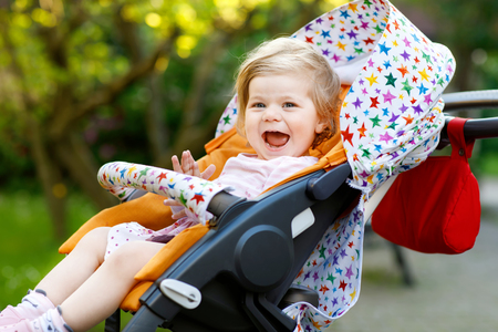 Portrait of little cute toddler girl sitting in stroller or pram and going for a walk. Happy cute baby child having fun outdoors 版權商用圖片